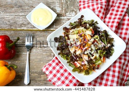 Fresh salad with tomato,cucumbers,Lettuce,corn,Purple lettuce with salad dressing Red tablecloth  - stock photo