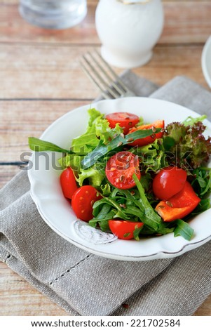 Fresh salad with tomatoes and arugula on a white plate, healthy food