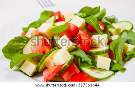 Fresh salad with tomatoes, arugula, cucumber and cheese cubes - stock photo