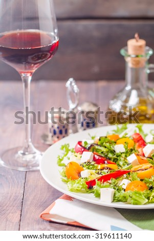 Fresh salad with tomatoes, paprika and feta cheese on wooden table. selective focus - stock photo