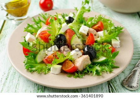 Fresh salad with tuna, tomatoes and cucumbers on lettuce leaves - stock photo