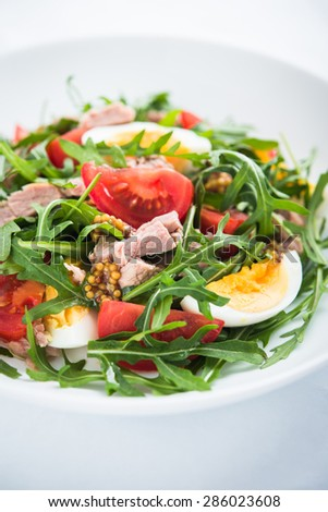 Fresh salad with tuna, tomatoes, eggs, arugula and mustard on white textured background close up. Healthy food. - stock photo