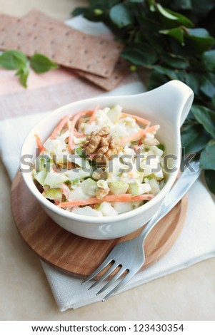 Fresh salad with white cabbage, carrot, apples and pears with walnuts and yogurt dressing in a bowl