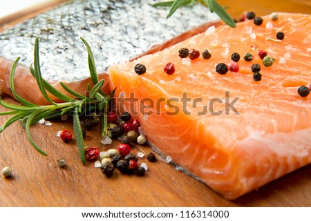 Fresh salmon fillet on wooden board with pepper and rosemary