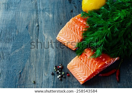 Fresh salmon fillet with aromatic herbs and spices over dark wooden texture - healthy food, diet or cooking concept.  - stock photo
