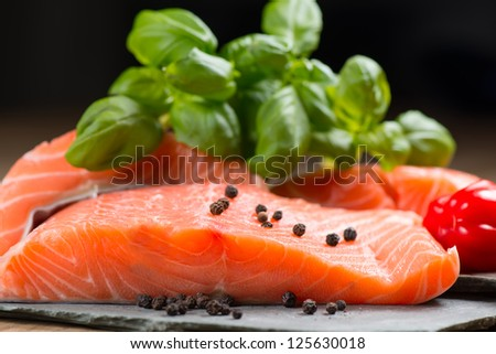 Fresh salmon fillet with basil and pepper on flat rocks - stock photo