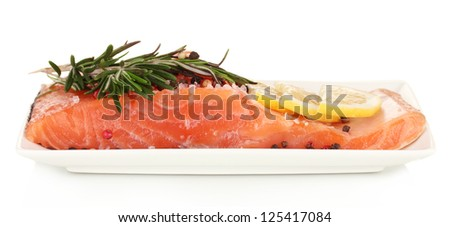Fresh salmon fillet with herbals and lemon slices on plate, isolated on white - stock photo