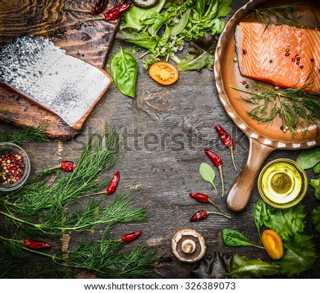 Fresh salmon fillet with ingredients for tasty cooking on rustic wooden background, top view, frame. Healthy food concept.