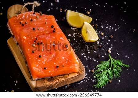 Fresh salmon fillet with lemon and dill on dark background - stock photo