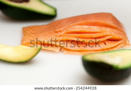 Fresh salmon fish with avocado on white table in preparation for sushi. Healthy and organic food.  - stock photo