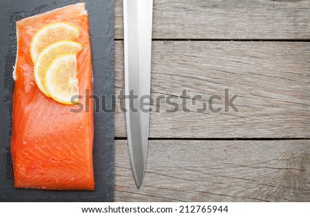 Fresh salmon fish with lemon and japan knife on wooden table with copy space - stock photo