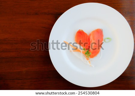 Fresh salmon in white dish on wood table