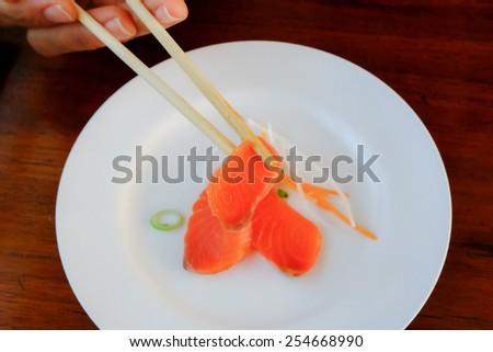 Fresh salmon in white dish on wood table - stock photo