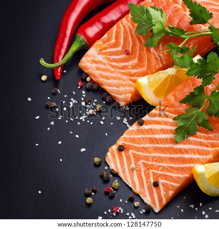 Fresh salmon on black plate - stock photo