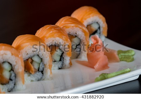 fresh salmon on top of a beautifully presented sushi roll on a white plate - stock photo