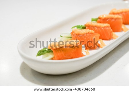 Fresh salmon roll in a white plate with selective focus - stock photo