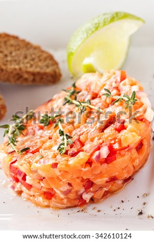 Fresh salmon salad with bread and lime - stock photo