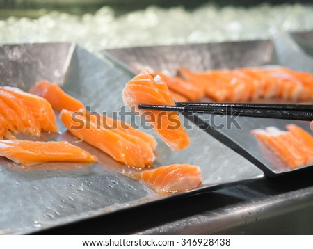 Fresh salmon sashimi picked up with chopsticks