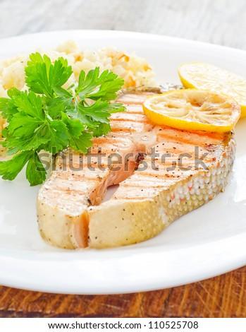 Fresh salmon served with rice parsley lemon - stock photo