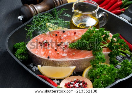 fresh salmon steak and ingredients for cooking on a grill pan, horizontal - stock photo