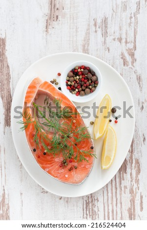 fresh salmon steak, lemon and pepper on white wooden background, top view, vertical - stock photo
