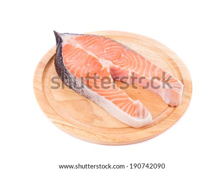 Fresh salmon steak on wooden platter. Isolated on a white background.