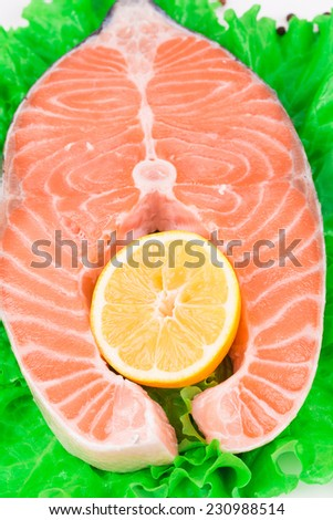 Fresh salmon steak with pepper and lemon. Whole background.