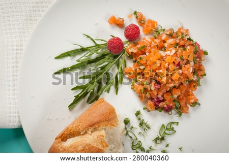 fresh salmon tartar with raspberries and rocket salad and herbs - stock photo
