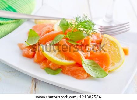 fresh salmon with lemon on the white plate - stock photo