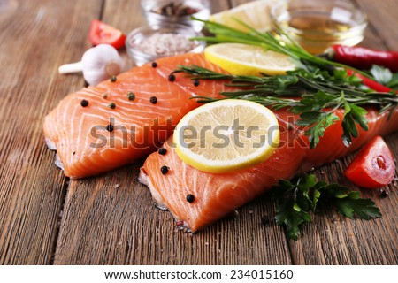 Fresh salmon with spices and lemon on wooden table - stock photo