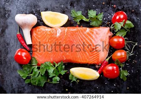 fresh salmon with vegetables on dark background - stock photo