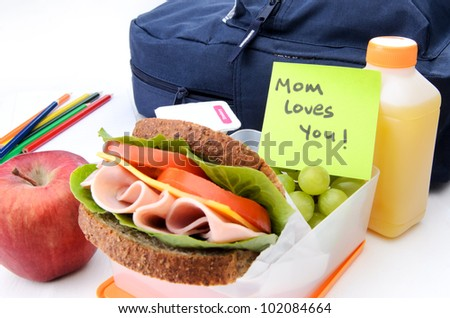 Fresh sandwich and apple with schoolbag and post-it note - stock photo