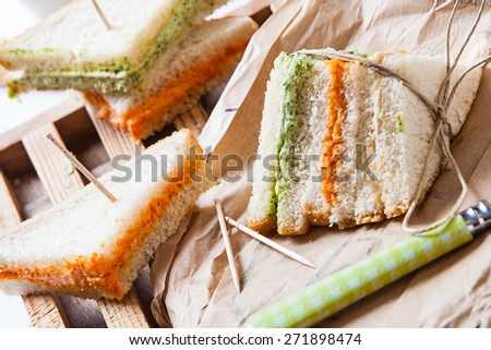 fresh sandwich filled with tomato and lettuce cream on paper - stock photo