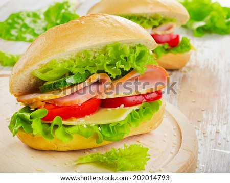 Fresh sandwich  on a wooden cutting board. Selective focus