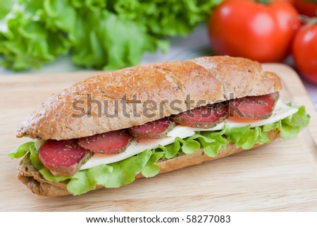 Fresh sandwich with dry meat and cheese on dietetic bread - stock photo