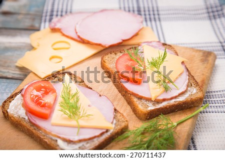 fresh sandwich with ham,cheese,tomatoes,parsley on plate in studio
