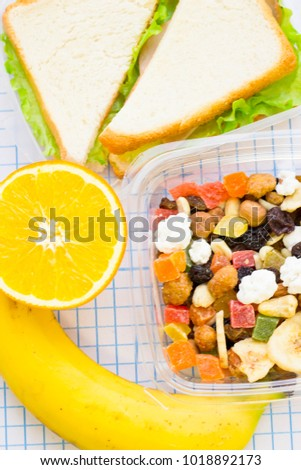 Fresh sandwich with lettuce in a plastic container, banana, orange and a plastic container of candied fruit and nuts, top view, close up, white squared paper background