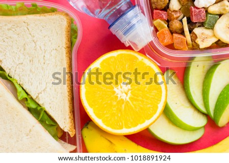 Fresh sandwich with lettuce , orange, banana, slices of green apple and a plastic container of candied fruit, top view, close up, rose background