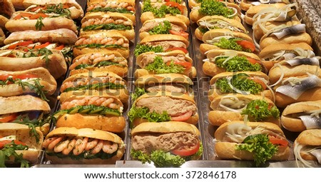 Fresh sandwiches with shrimp, herring, tomato, lettuce salad, pate, cucumber and onion - stock photo