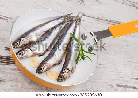 Fresh sardines with garlic and fresh herbs on pan on wooden background, top view. Culinary healthy seafood eating.  - stock photo