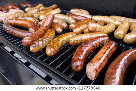 Fresh sausage and hot dogs grilling outdoors on a gas barbecue grill. - stock photo