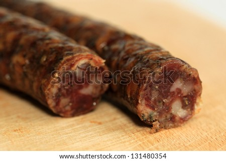 Fresh sausage on wooden plate