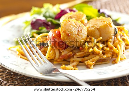 Fresh scallops with linguine pasta and tomato sauce with a side salad