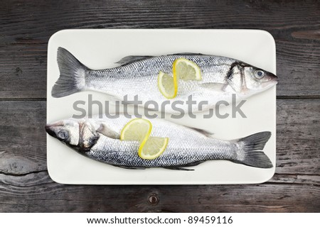 Fresh sea bass in a white plate, on a wooden surface. - stock photo