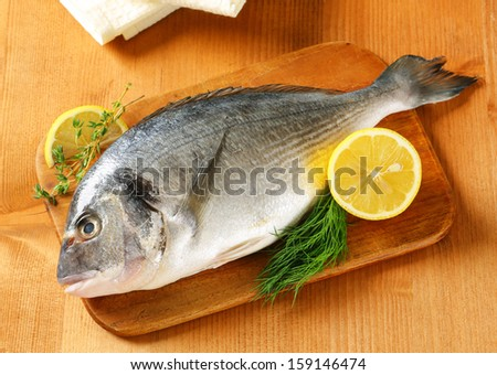 fresh sea bream with lemons and herbs, on a wooden cutting board - stock photo