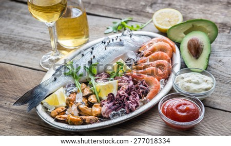 Fresh seabass with seafood on the tray - stock photo