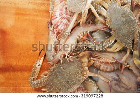 Fresh seafood on wooden background, fresh squids, crabs ans shrimps with seashells - stock photo