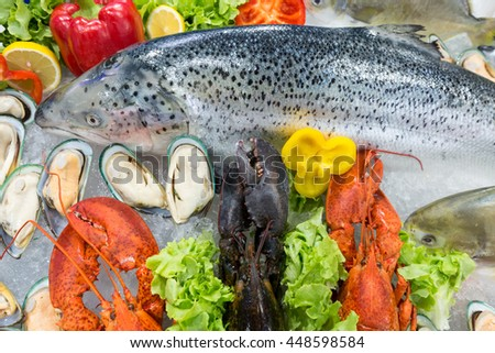 Fresh seafood, Salmom, lobsters,and Australian mussels displayed on crushed ice at fish market stall. - stock photo
