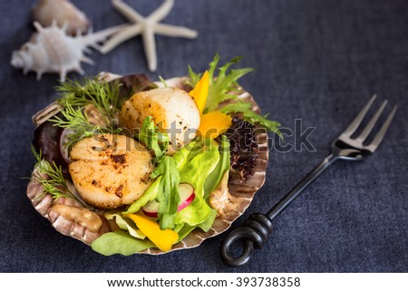 Fresh seared sea scallops salad with mango, radish, avocado on scallop shell with fork on the side - stock photo