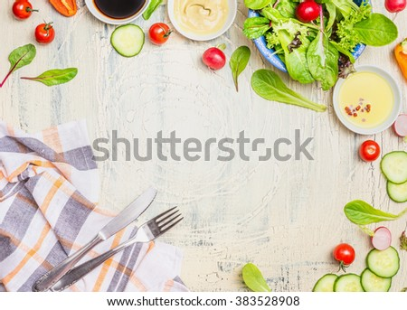 Fresh seasonal organic vegetables salad preparation with dressings ,ingredients cutlery  and kitchen checked napkin on light rustic background, top view, frame. Healthy eating or clean food concept. - stock photo